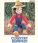 Country Bumpkin boy soft sculpture doll wearing overalls and straw hat.